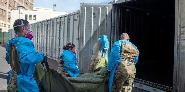 In this Jan. 12, 2021 photo provided by the Los Angeles County Department of Medical Examiner-Coroner, National Guard members assisting with processing COVID-19 deaths, placing them into temporary storage at the medical examiner-coroner's office in Los Angeles.