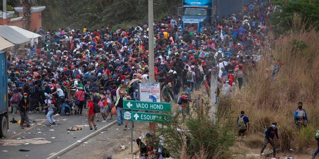 Honduran migrants, 상단, stand between cargo trucks as they confront Guatemalan soldiers and police blocking them from advancing toward the US, on the highway in Vado Hondo, 과테말라, 월요일, 1 월. 18, 2021.