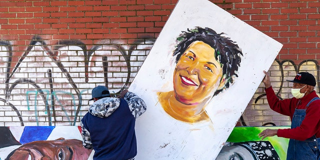 Artists set up a painting of Stacey Abrams in the King Historic District on Monday, Jan. 18, 2021, in honor of Martin Luther King Jr. Day, in Atlanta. (Associated Press)