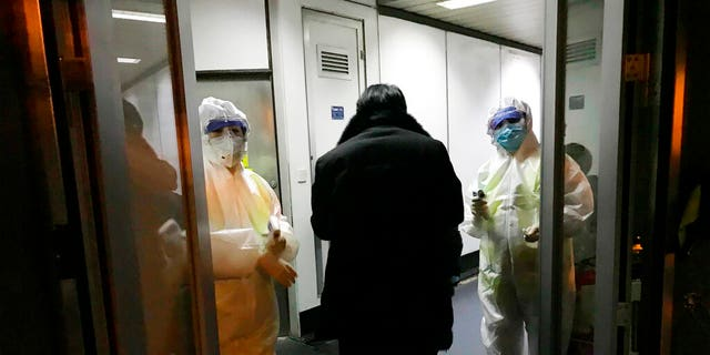 FILE: Health Officials in hazmat suits wait at the gate to check body temperatures of passengers arriving from the city of Wuhan, at the airport in Beijing, China.