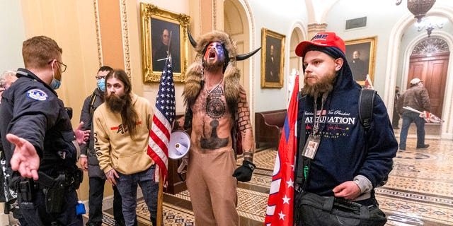 Jacob Chansley, center with fur hat, is seen inside the U.S. Capitol during a riot on Jan. 6, 2021. (Associated Press)