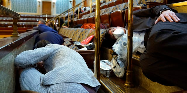 In this Wednesday, Jan. 6, 2021 file photo, people shelter in the House gallery as rioters try to break into the House Chamber at the U.S. Capitol in Washington. (AP Photo/Andrew Harnik, File)
