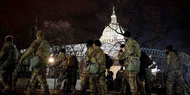 National Guard stand outside the Capitol on Inauguration Day in Washington, D.C. on Wednesday, Jan. 20, 2021. (Erin Schaff/The New York Times via AP, Pool)