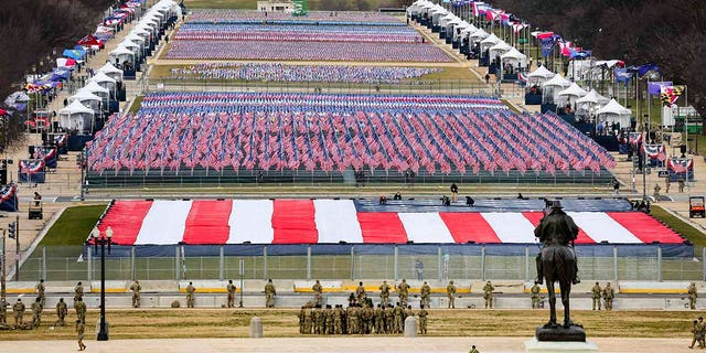 """Members of the National Guard look on as American flags decorate the """"Field of Flags"""" at the National Mall ahead of President-elect Joe Biden's inauguration ceremony, Wednesday, Jan. 20, 2021, in Washington. (Tasos Katopodis/Pool Photo via AP)"""