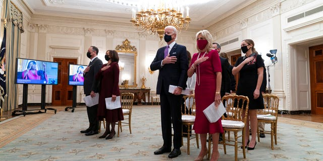 Doug Emhoff, left, Vice President Kamala Harris, President Joe Biden, and first lady Jill Biden, stand during a performance of the national anthem during a virtual Presidential Inaugural Prayer Service. (AP Photo/Alex Brandon)
