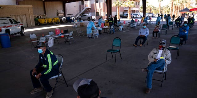 Farmworkers wait in the holding area after getting the Pfizer-BioNTech COVID-19 vaccine at Tudor Ranch in Mecca, Calif., Thursday, Jan. 21, 2021.
