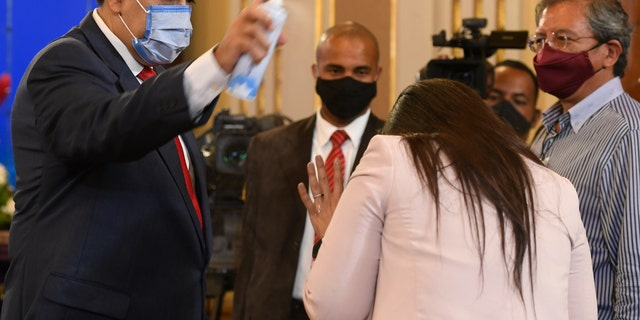 FILE - In this Dec. 8, 2020 file photo, Venezuela's President Nicolas Maduro playfully sprays a journalist with disinfectant as he exits a press conference at Miraflores Presidential Palace in Caracas, Venezuela, amid the new coronavirus pandemic. Attorneys for the cash-strapped government blame the impact of U.S. sanctions for its inability to make an initial $  18 million down payment to the United Nations for doses of the U.N.-supplied vaccines, whose deadline has already passed. (AP Photo/Matias Delacroix, File)