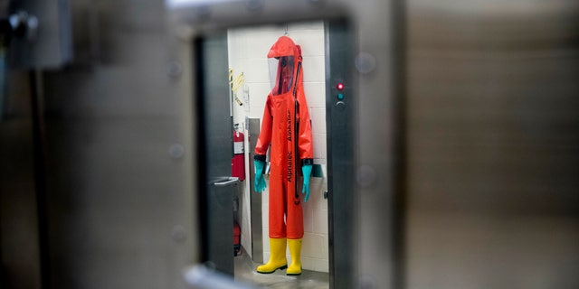 FILE - In this March 19, 2020, file photo, a biosafety protective suit for handling viral diseases are hung up in a biosafety level 4 training facility at U.S. Army Medical Research and Development Command at Fort Detrick in Frederick, Md., where scientists are working to help develop solutions to prevent, detect and treat the coronavirus. China is trying to spread doubt about the effectiveness of Western vaccines and the origin of the coronavirus as a World Health Organization-selected team of scientists are in the city where the pandemic first broke out. (AP Photo/Andrew Harnik, File)