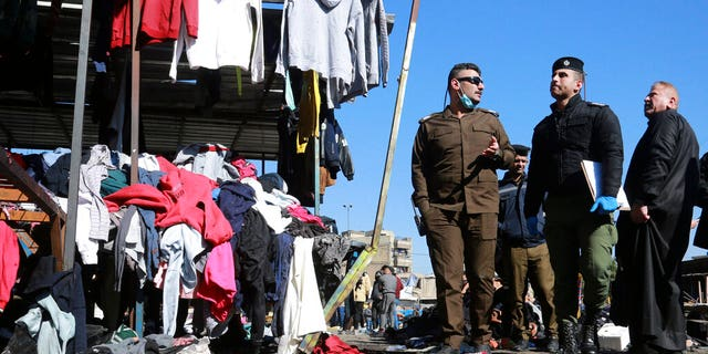 FILE: Security forces work at the site of a deadly bomb attack in a market selling used clothes, in Baghdad, Iraq.