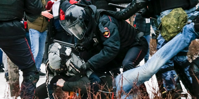 Riot police detain a demonstrator with a bloody face during a protest against the jailing of opposition leader Alexei Navalny in Pushkin square in Moscow, Russia, Saturday, Jan. 23, 2021. (AP Photo/Alexander Zemlianichenko)