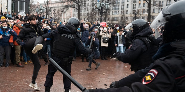 A demonstrator clashes with a police officer during a protest against the jailing of opposition leader Alexei Navalny in Pushkin square in Moscow, Russia, Saturday, Jan. 23, 2021. (AP Photo/Victor Berezkin)