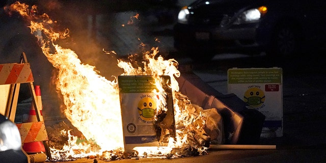A car drives near burning garbage and a safety sign for mask COVID-19 during a protest against police brutality, late Sunday, January 24, 2021, in downtown Tacoma, Wash., South of Seattle.  (AP Photo / Ted S. Warren)