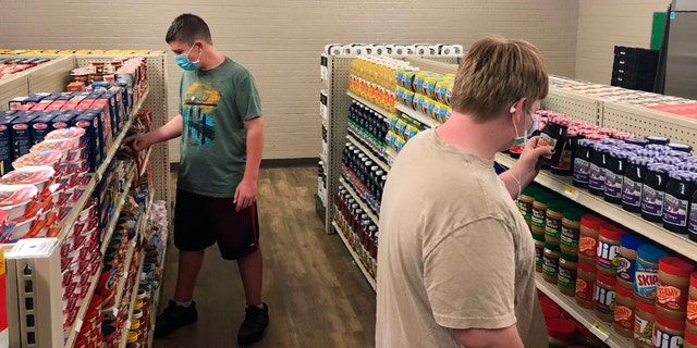 Hunter Weertman, 16, left, stocks shelves and takes inventory while working as a manager of the student-led free grocery store at Linda Tutt High School in Sanger, Texas. (Anthony Love via AP)