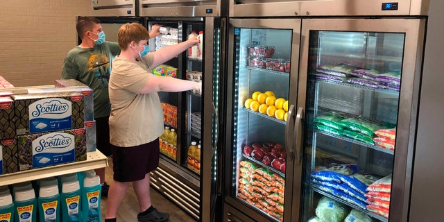 Hunter Weertman, 16, left, works alongside a fellow student to stock the refrigerator in the student-led free grocery store at Linda Tutt High School. (Anthony Love via AP)