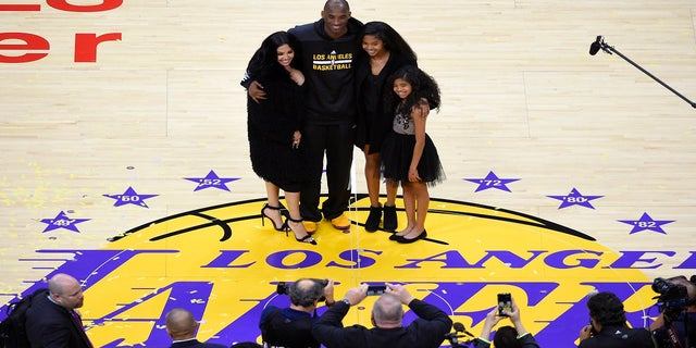 In this April 13, 2016, file photo, Los Angeles Lakers' Kobe Bryant poses for pictures with his wife Vanessa, left, and daughters Natalia, second from right, and Gianna as they stand on the court after an NBA basketball game against the Utah Jazz, in Los Angeles.