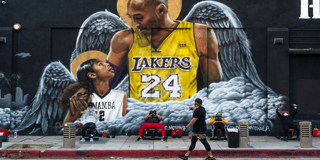 People lift weights on a sidewalk outside the Hardcore Fitness gym, due to COVID-19 restrictions, under a mural honoring NBA star Kobe Bryant and his daughter Gigi near Staples Center in downtown Los Angeles, Monday, Jan. 25, 2021. (AP Photo/Damian Dovarganes)