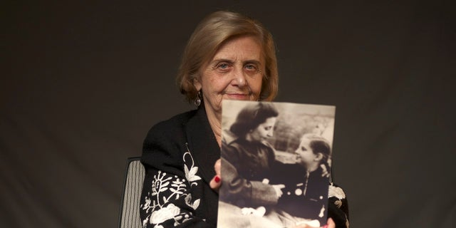 This photo provide by the World Jewish Congress, Tova Friedman, an 82-year-old Polish-born Holocaust survivor holding a photograph of herself as a child with her mother, who also survived the Nazi death camp Auschwitz, in New York, Friday, Dec.13, 2019. (World Jewish Congress via AP)
