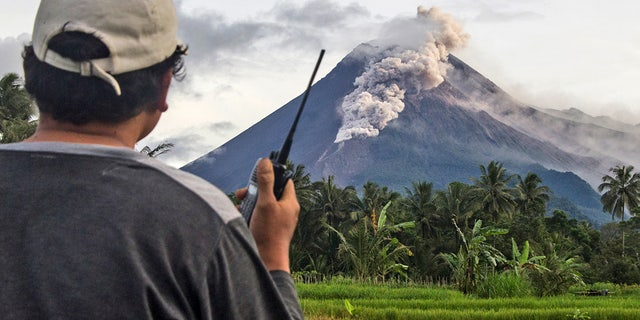 A volunteer uses his walkie-talkie as he monitors Mount Merapi during an eruption in Sleman, Wednesday, Jan. 27, 2021. Indonesia's most active volcano erupted Wednesday with a river of lava and searing gas clouds flowing 1,500 meters (4,900 feet) down its slopes. (AP Photo/Slamet Riyadi)