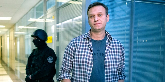 FILE - In this Dec. 26, 2019 파일 사진, Russian opposition leader Alexei Navalny speaks to the media in front of a security officer standing guard at the Foundation for Fighting Corruption office in Moscow, 러시아. Navalny was jailed soon after arriving to Moscow after authorities accused him of violating of the terms of his 2014 fraud conviction. A court on Thursday Jan. 28, 2021, is to hear an appeal on the ruling to remand him into custody. Next week, another court will decide whether to send him to prison for several years for the alleged violations. (AP Photo/Alexander Zemlianich파일, File)