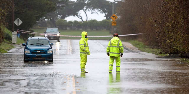 San Luis Obispo County workers forecast flooding on a road in Cambria, California, on Thursday, January 28, 2021. After losing land on Tuesday in northern California, a storm aimed at the central coast, where the two-day-long precipitation approached a total of 14 inches (35.5 centimeters) in San Luis Obispo County, according to the National Weather Service.  (Laura Dickinson / The Tribune (by San Luis Obispo) via AP)