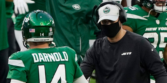New York Jets head coach Adam Gase shakes hands with quarterback Sam Darnold (14) after the Jets scored a touchdown during the second half of an NFL football game against the Los Angeles Rams Sunday, Dec. 20, 2020, in Inglewood, Calif. (AP Photo/Ashley Landis)