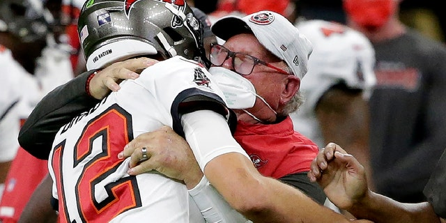 Tampa Bay Buccaneers quarterback Tom Brady hugs head coach Bruce Arians on the sidelines during the second half of an NFL divisional-round playoff football game against the New Orleans Saints, Sunday, Jan. 17, 2021, in New Orleans. The Buccaneers won 30-20. (AP Photo/Butch Dill)