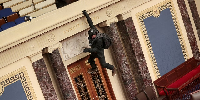 A protester is seen hanging from the balcony in the Senate Chamber on Jan. 6, 2021, a Washington, D.C. (Win McNamee/Getty Images)