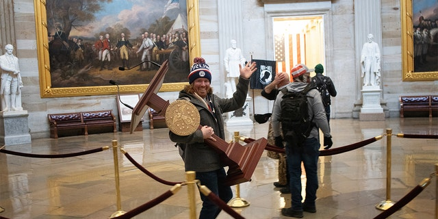 A pro-Trump protester carries the lectern of U.S. Speaker of the House Nancy Pelosi through the Rotunda of the U.S. Capitol Building after a pro-Trump mob stormed the building on Jan. 6, 2021.
