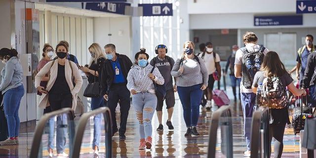 I viaggiatori che indossano maschere protettive attraversano l'aeroporto internazionale di Dallas / Fort Worth (DFW) a Dallas, Texas.