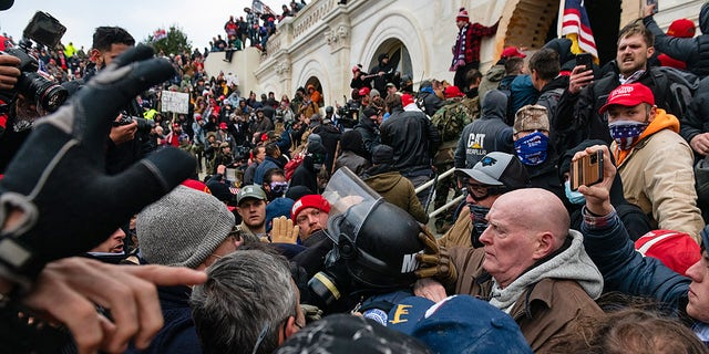 Protesters drag and seize the Metropolitan Police while trying to enter the US Capitol (Eric Lee / Bloomberg via Getty Images)