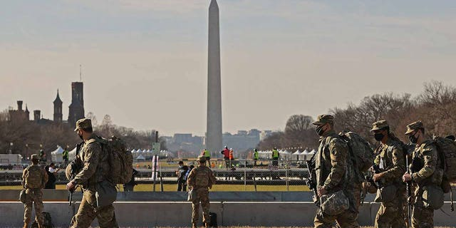National Guard troops move along the National Mall the day after the House of Representatives voted to impeach President Donald Trump for the second time on Jan. 14.