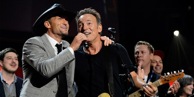 Bruce Springsteen (right) explained how country crooner Tim McGraw (left) cheered him up after losing 'Album of the Year.'