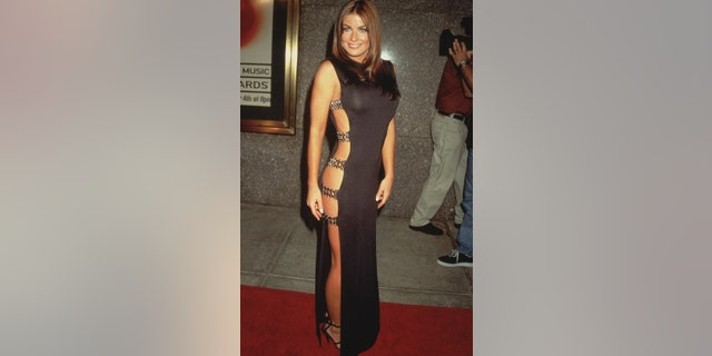 American model and actress Carmen Electra posing outdoors on a red carpet in a long black sheath dress with cutaway sides at the MTV Video Music Awards, Radio City Music Hall, New York City. Photo circa 1997.
