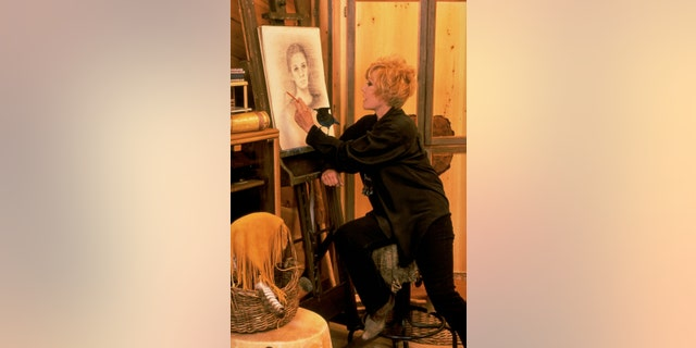 Retired actress Kim Novak sketching a portrait of an unidentified girl as a pet blue jay stands on her arm.