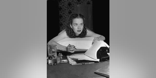 Susan Peters writing on a hospital cart in her home. The actress kept busy as doctors originally insisted she would walk again.