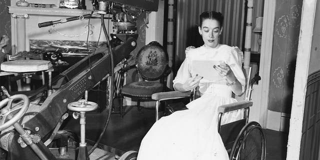 Actress Susan Peters pictured reading from her notes in front of a WPTZ television camera, as she sits in a wheelchair, for her show 'Miss Susan', circa 1951.