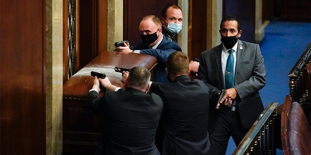 U.S. Capitol Police with guns drawn stand near a barricaded door as protesters try to break into the House Chamber at the U.S. Capitol on Jan. 6, in Washington. (AP Photo/Andrew Harnik)