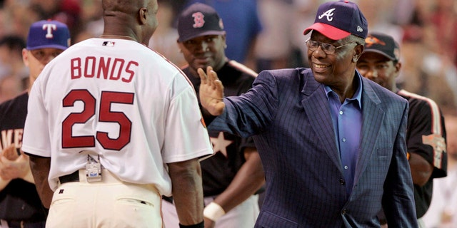 FILE- In this July 12, 2004, file photo, home run record holder Hank Aaron greets San Francisco Giants slugger Barry Bonds before the start of the All-Star Home Run Derby in Houston. (AP Photo/Eric Gay, File)