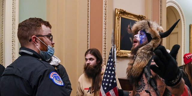 US Capitol police officers try to stop supporters of President Trump, including Jacob Chansley (R), a QAnon supporter known for his painted face and horned hat, to enter the Capitol on Jan. 6, 2021, in Washington, D.C.