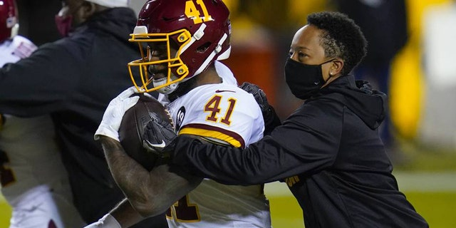 Full-year coaching intern Jennifer King, right, works with Washington Football Team running back J.D. McKissic (41) before the team's NFL wild-card playoff football game against the Tampa Bay Buccaneers, Saturday, Jan. 9, 2021, in Landover, Md.