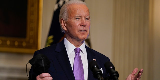 In this Jan. 26, 2021, photo, President Joe Biden holds his face mask as he speaks on COVID-19, in the State Dining Room of the White House in Washington. (AP Photo/Evan Vucci)