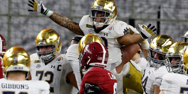 Notre Dame running back Kyren Williams, top, is lifted by offensive lineman Landon Dickerson (69) after Williams' touchdown run as Alabama linebacker Christian Harris (8) looks on in the first half of the Rose Bowl NCAA college football game in Arlington, Texas, Jan. 1. (AP Photo/Roger Steinman)