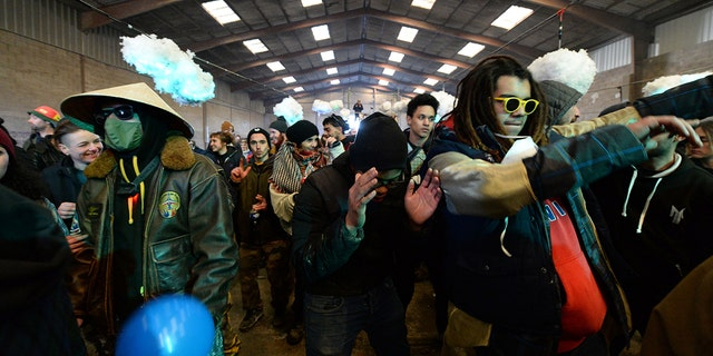 """People dance during a party near a disused hangar in Lieuron about 40km (around 24 miles) on south of Rennes, on January 1, 2021. - A wild party that began on December 31 evening in Lieuron, still gathered on January 1 around 2,500 participants """" from different departments and from abroad """", according with a press release from the prefecture of Ille-et-Vilaine. (Photo by JEAN-FRANCOIS MONIER / AFP) (Photo by JEAN-FRANCOIS MONIER/AFP via Getty Images)"""