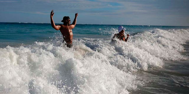 U.S. tourist Latron Evans and his partner Nika, frolicking ocean waters at the beach in Tulum, Quintana Roo state, Mexico, Monday, Jan. 4, 2021. Evans, a Mississippi firefighter, said he was impressed by the health measures due to the new coronavirus pandemic. (AP Photo/Emilio Espejel)