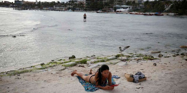 A tourist relaxes on the shore of Mamitas beach amid the new coronavirus pandemic in Playa del Carmen. (AP Photo/Emilio Espejel)