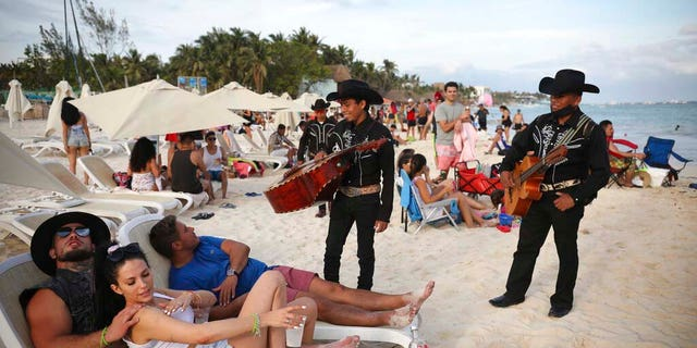 "Roving musicians ""Los Compas"" approach a group of tourists on the shore of Mamitas beach, in Playa del Carmen. (AP Photo/Emilio Espejel)"