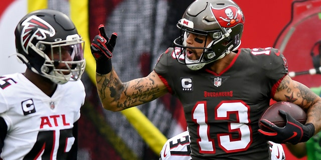 Tampa Bay Buccaneers wide receiver Mike Evans (13) reacts after catching a pass in front of Atlanta Falcons linebacker Deion Jones (45) during the first half of an NFL football game Sunday, Jan.. 3, 2021, in Tampa, Fla. Evans' reception put him over the 1,000-yard mark for the season. (AP Photo/Jason Behnken)