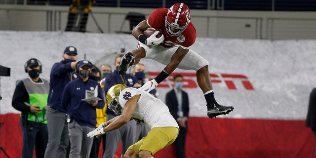 Alabama running back Najee Harris (22) hurdles Notre Dame cornerback Nick McCloud (4) as he carries the ball for a long gain in the first half of the Rose Bowl NCAA college football game in Arlington, Texas, Jan. 1, 2021. (AP Photo/Michael Ainsworth)