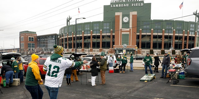 Fans toss bean bags outside of Lambeau Field before an NFL divisional playoff football game between the Los Angeles Rams and Green Bay Packers, Saturday, Jan. 16, 2021, in Green Bay, Wis. (AP Photo/Mike Roemer)