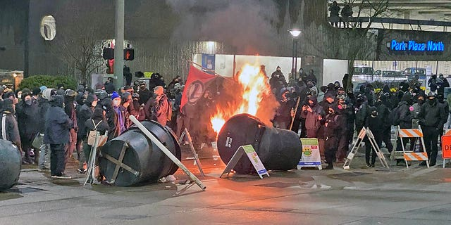 Antifa activists, dressed in black blocks, set small fires in an intersection at Frost Park in Tacoma, Wash., Before their destructive march.